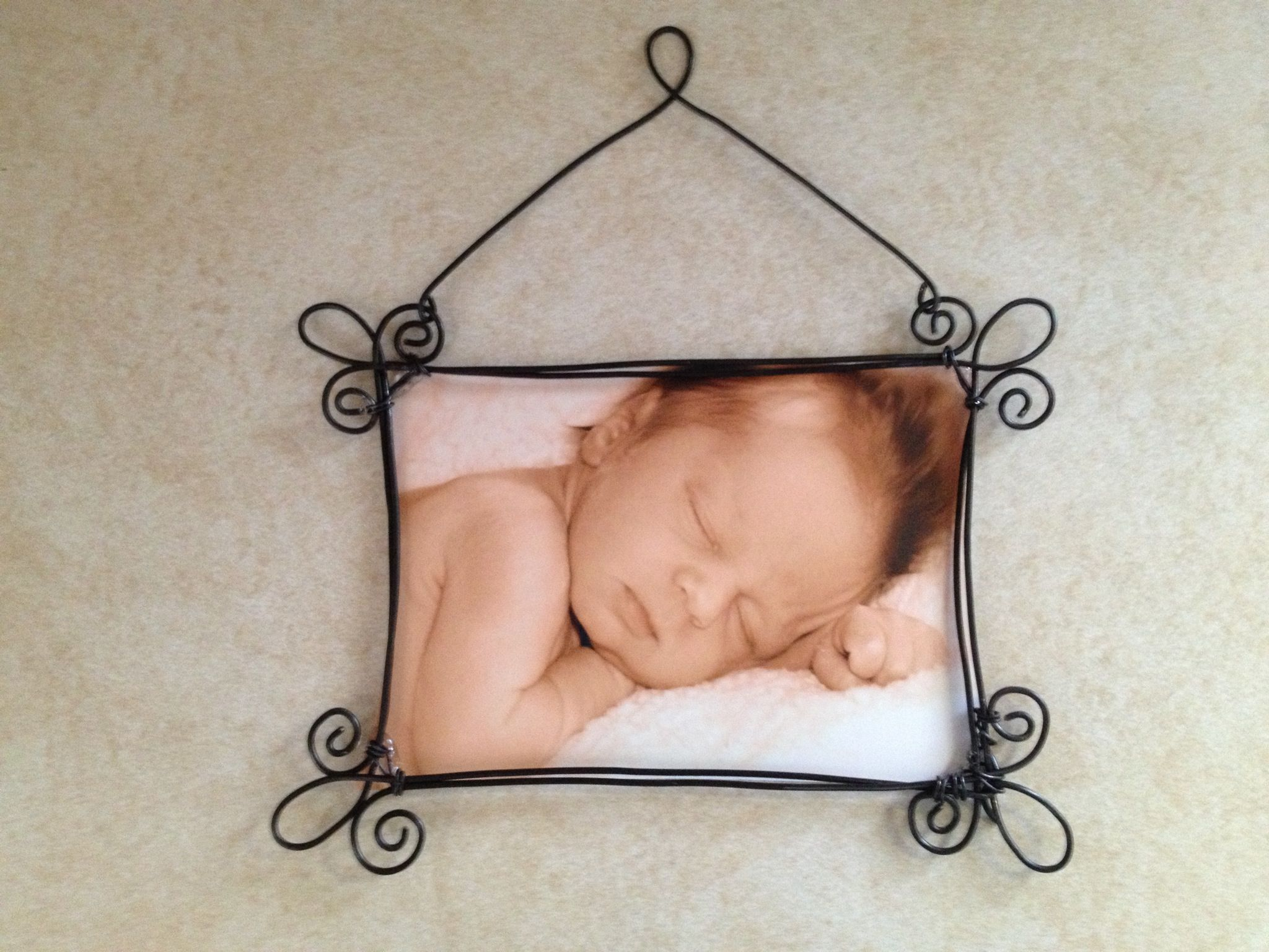 Wire frame with grand baby's picture.  The frame was made with rebar wire which was very stiff and difficult to bend.