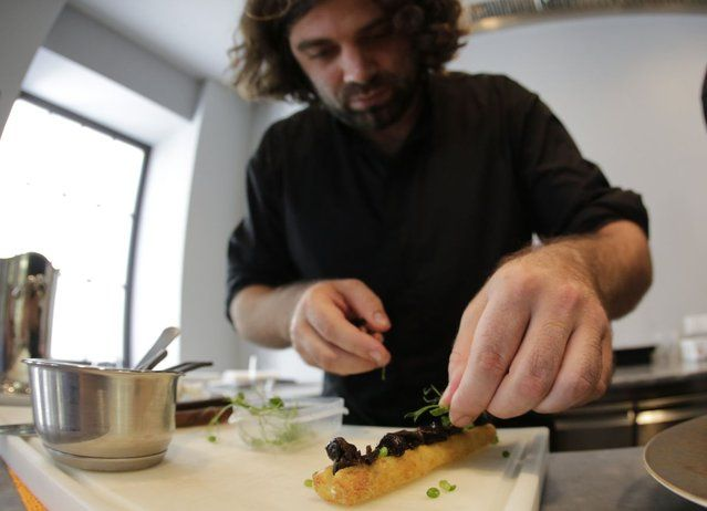 Austrian chef Konstantin Filippou prepares a snail dish in his gourmet restaurant in Vienna July 12, 2013. Andreas Gugumuck owns Vienna's largest snail farm, exporting snails, snail-caviar and snail-liver all over the world. The gourmet snails are processed using old traditional cooking techniques and some are sold locally to Austrian gourmet restaurants. (Photo by Leonhard Foeger/Reuters) http://avaxnews.net/fact/Snail_Farming_in_Austria.html