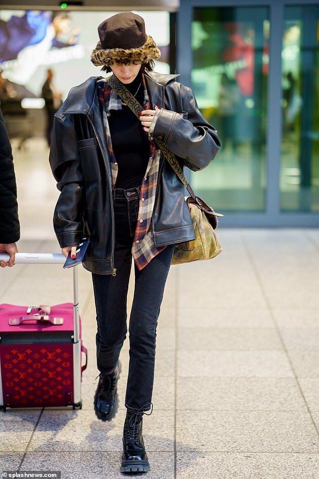 On her way: Bella kept her head down as she made her way through the terminal, with a memb...