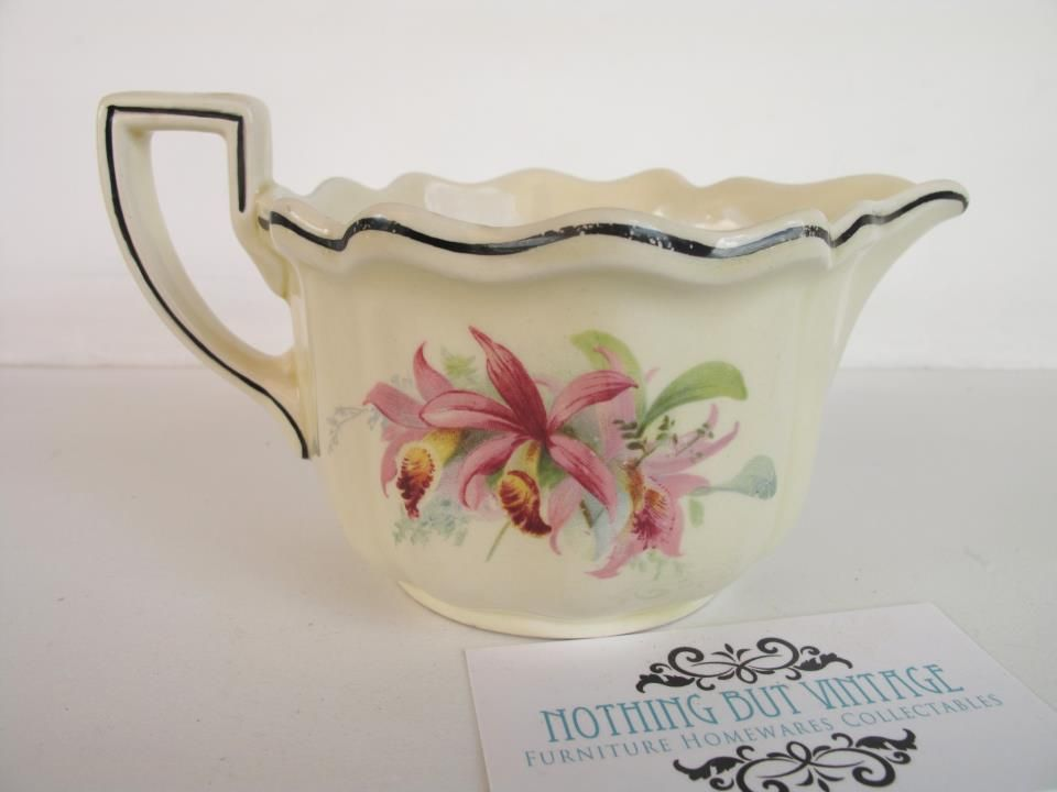 Royal Doulton England gravy jug, c1930, art deco shape with 2 different orchid prints on each side, light wear to black line around rim, no chips or cracks.