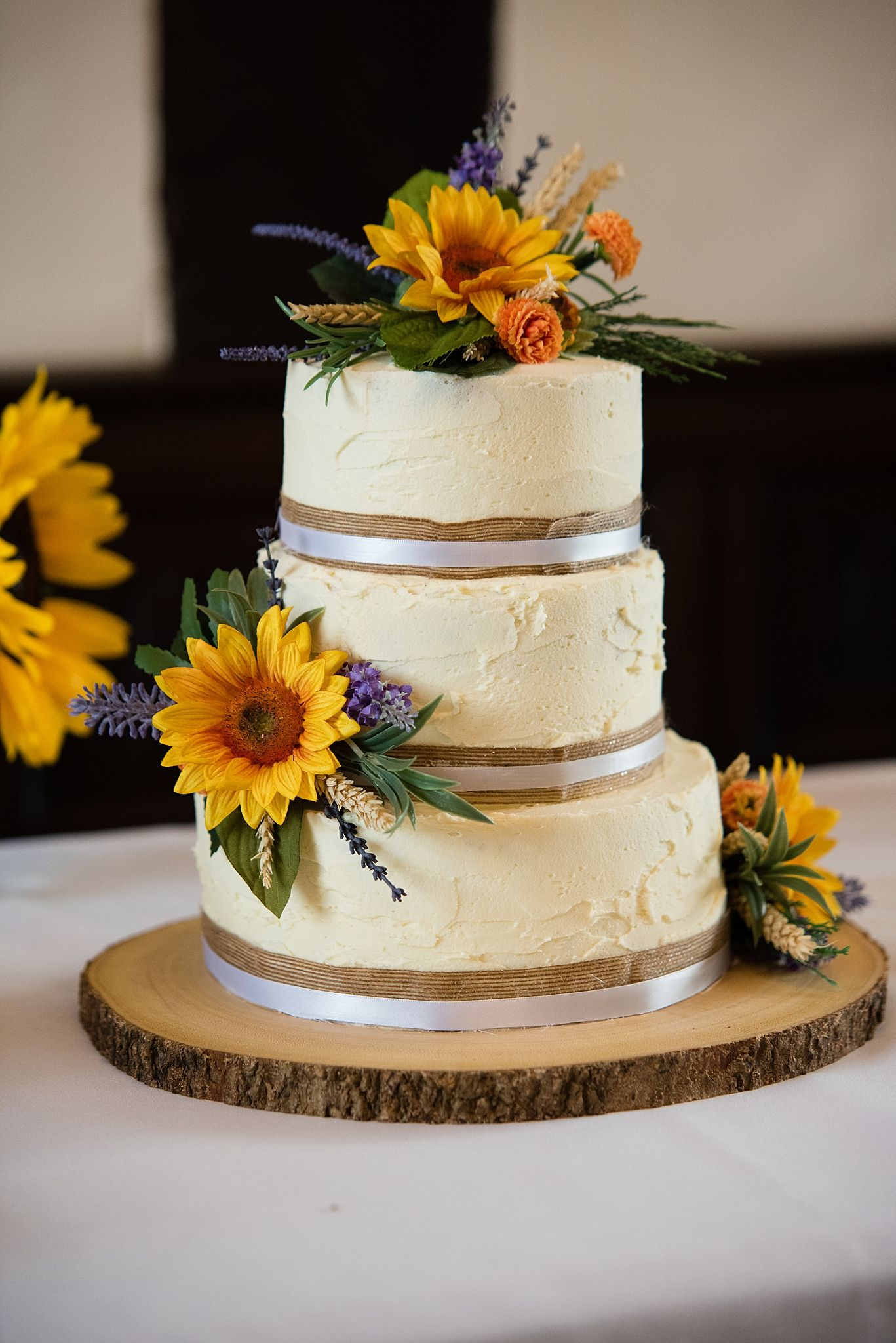 Rustic three tier wedding cake decorated with sunflowers