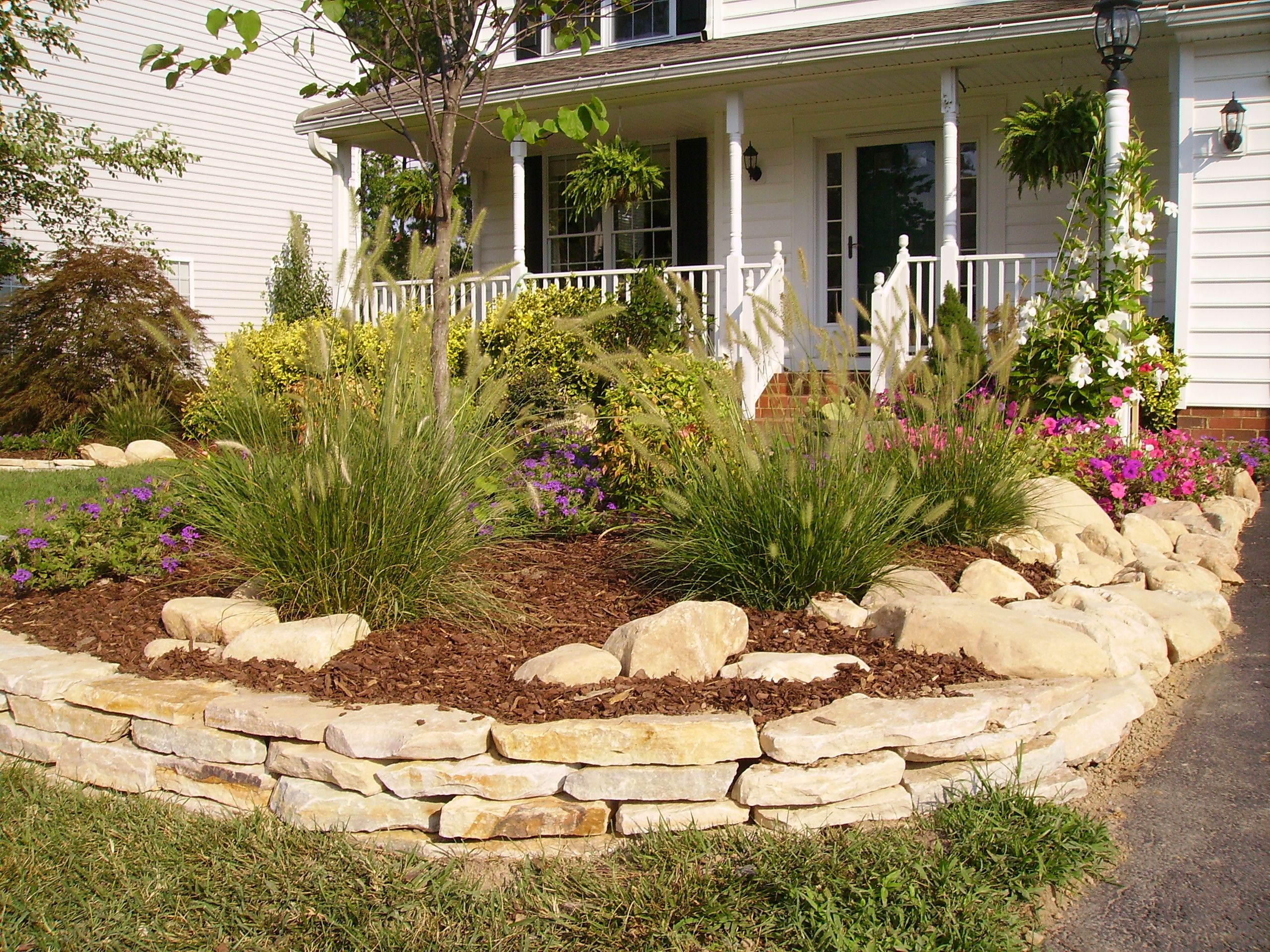 In this photo, the stacked stone is edging the flowerbed and ...