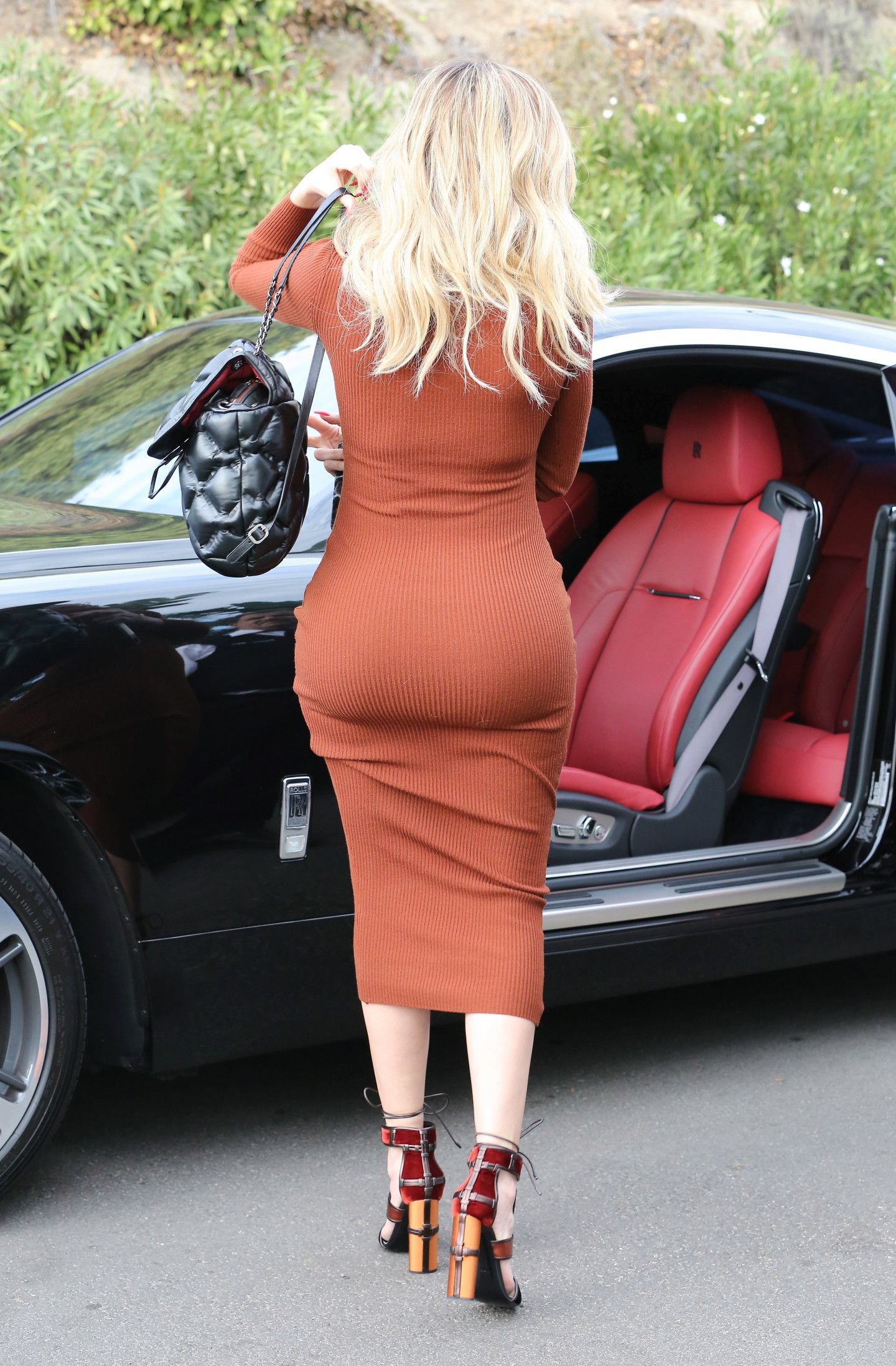 Khloe Kardashian rivals big sister Kim showing off her bum in a skintight dress