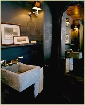 A dramatic bathroom with dark walls, ambient lighting and a concrete sink.