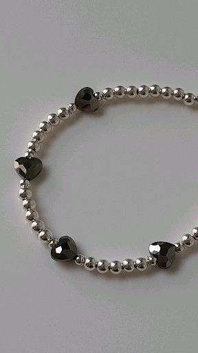 """🖤Mavey Black Hearts Bracelets🖤  An elegant sterling silver adjustable bracelet which features twinkling 8mm Swarovski® Heart Crystals.  Sterling silver round beads complete the look with a gorgeous 6mm sterling silver heart charm to add a finishing touch.  Beautiful shimmers of black, grey and silver tones play through these beautiful crystal hearts, changing in different lighting.  Simply slide the """"Silver Slider Bead"""" down the chain to loosen and back up again to tighten."""
