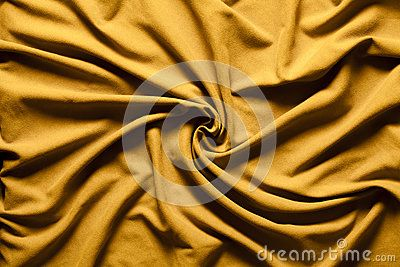 A fabric with gold colored curves and waves with draped effect. Intense color and large depth of field.