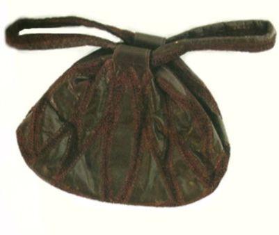 Bolsa de couro, costurada com bordados e forro de seda vermelha com alças em forma de laço