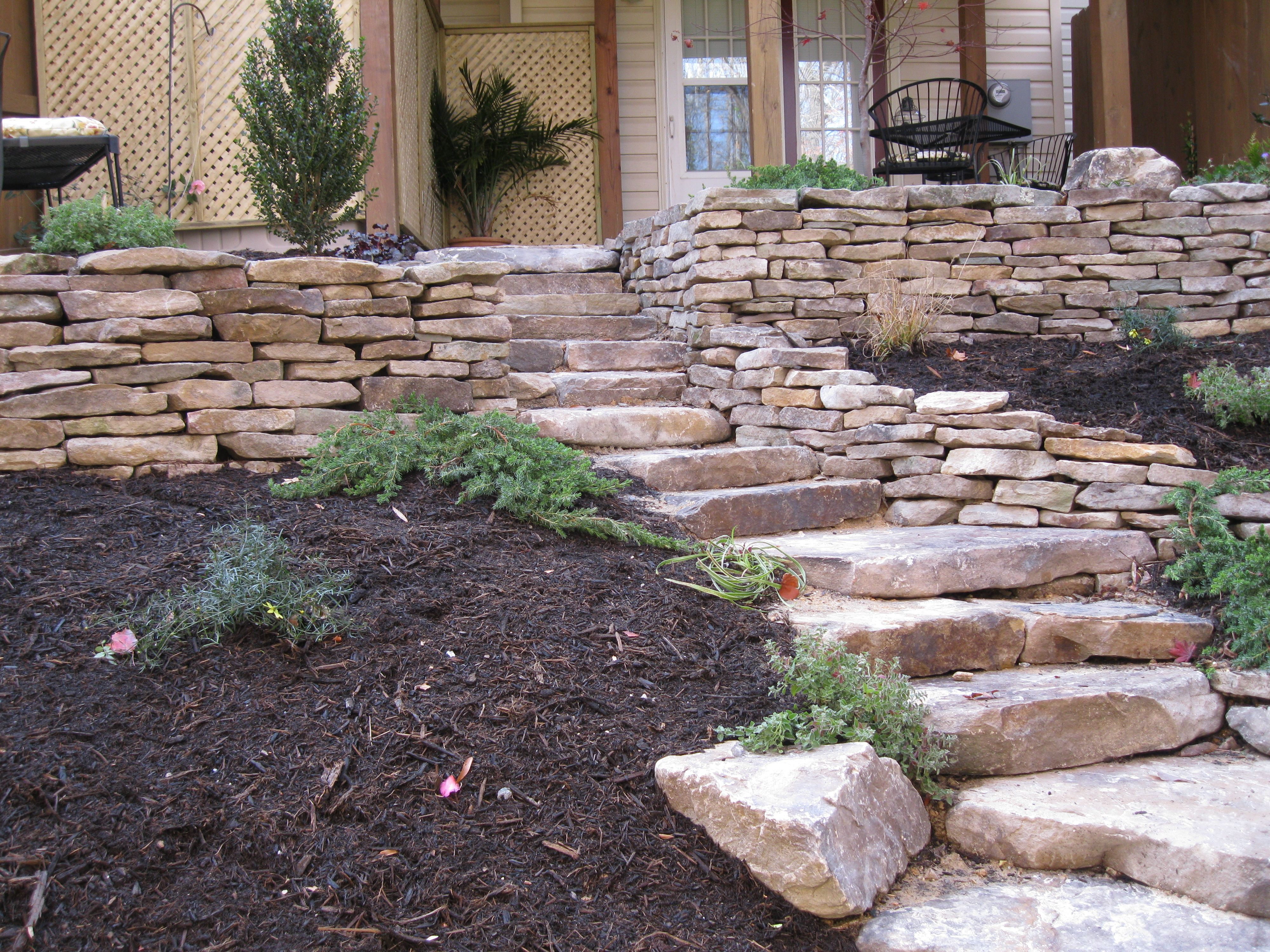 these stacked stone walls were built to level a sloped backyard
