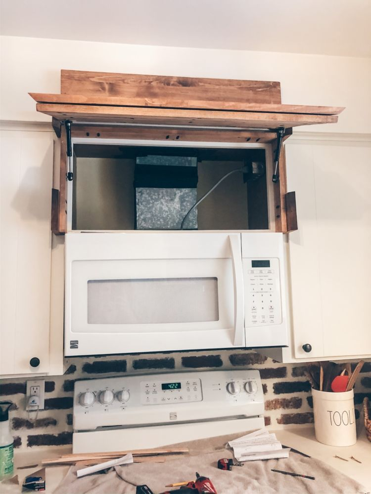 love this farmhouse home diy dea! it looks like a range hood, but it has storage hidden with hinges! I can't believe how nice it looks in their kitchen. #homediy #farmhousediy  we've been looking for ways to add storage around our small home! A while back, I took off the cabinet doors above our microwave and covered the space with a decorative cover (shown below) that didn't function, but now we've decided to make it useful with some hinges!    You can see how I built the hood vent cover here.