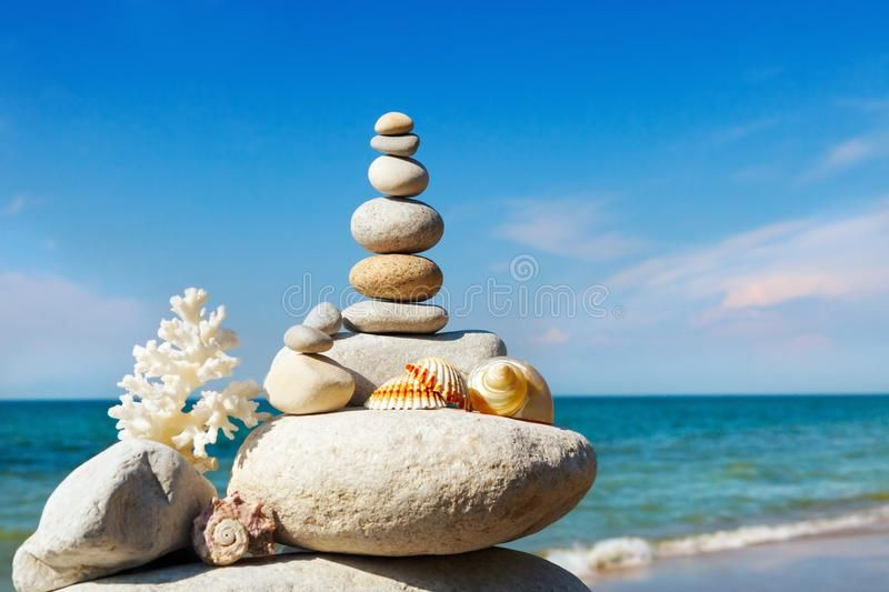 Rock zen of white stones shells and coral on a background of the summer sea and