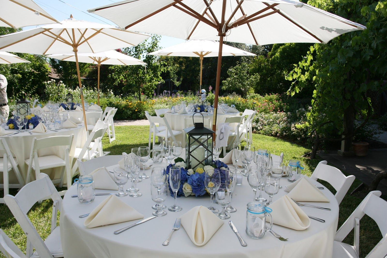Reception Tables With White Patio Umbrellas Scattered Between Them. A  Wonderful Garden Party Look  Plus They Keep The Tables Shaded From The Sun.