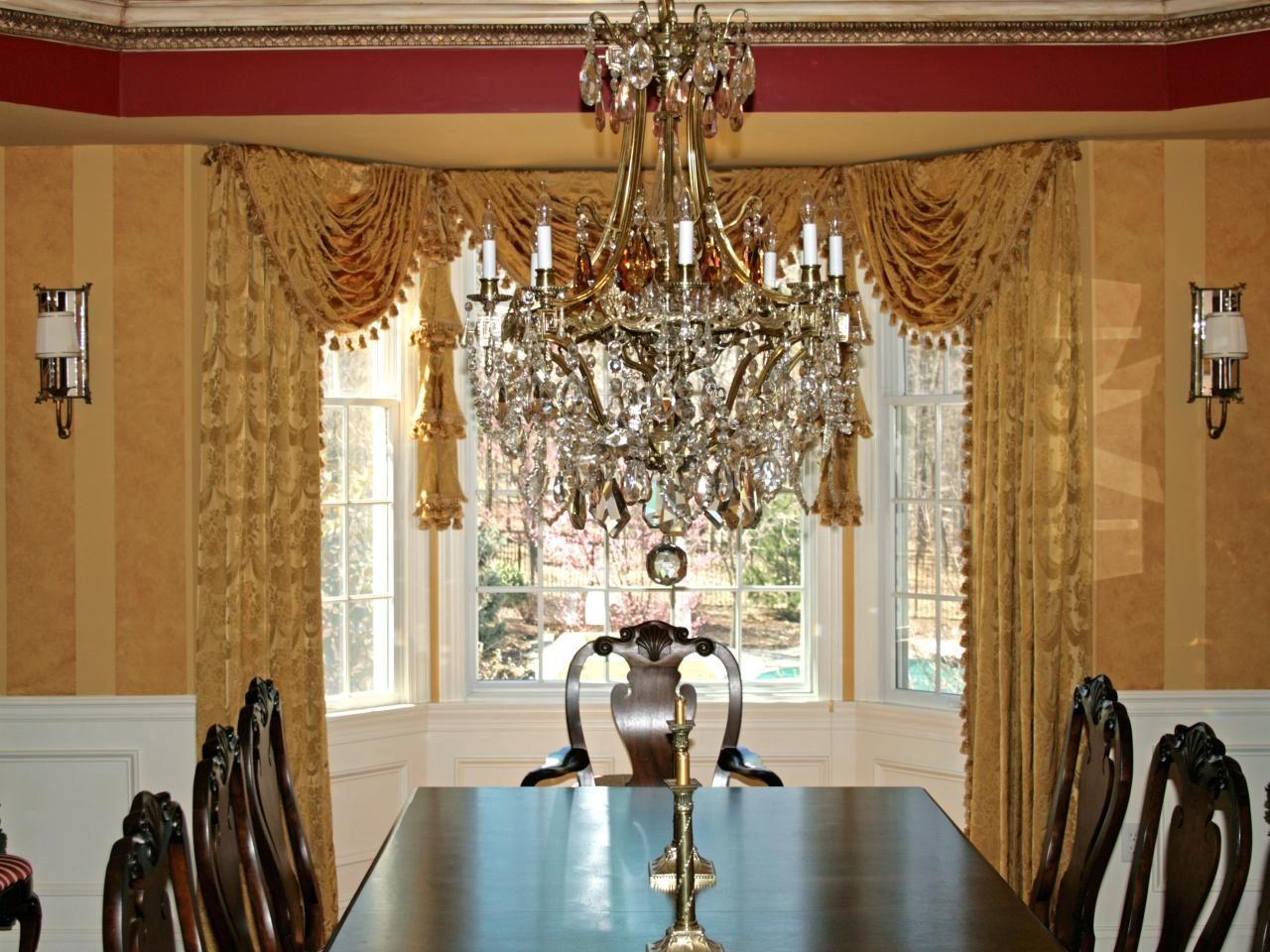 An ornate crystal and gold chandelier adds sparkle to this for Formal dining room window treatments