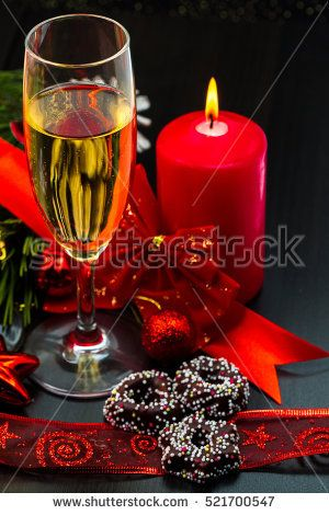 Christmas or New Year. Champagne in glasses with candles, panettone and gift with red satin bow. Copy-space. Festive Concept