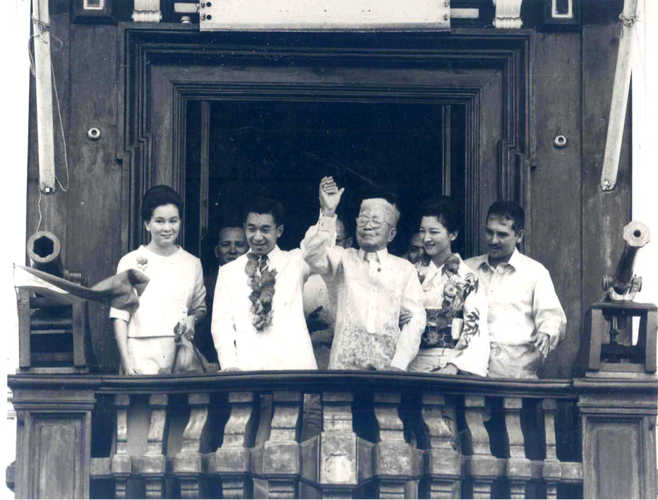 Crown Prince Akihito raises the right arm of former President Emilio Aguinaldo at the Independence Balcony of the Aguinaldo Mansion in Kawit, Cavite during the Crown Prince's state visit on November 5-10, 1962. In the photo: Irene Viola-Roces, Crown Prince Akihito, President Aguinaldo, and Crown Princess Michiko, and Secretary of Education Alejandro Roces. This photo will be given by President Benigno S. Aquino III to Emperor Akihito in his upcoming state visit to Japan on June 2-5, 2015…
