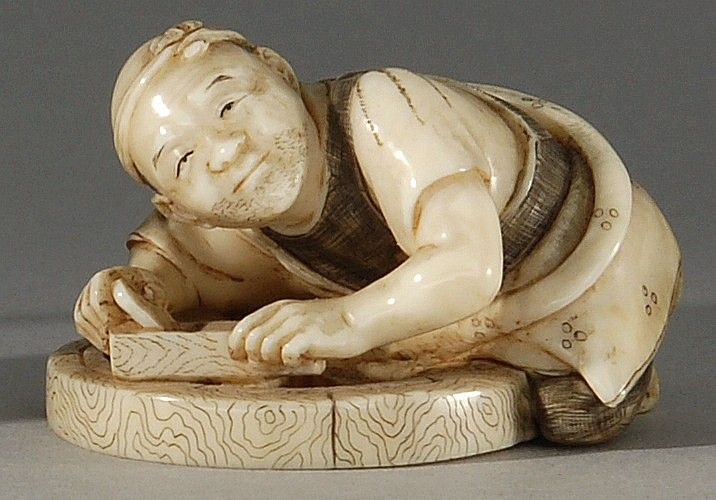 IVORY NETSUKE Late 19th Century  By Shogetsu. In the form of a wheelwright working on a cart wheel. Signed.