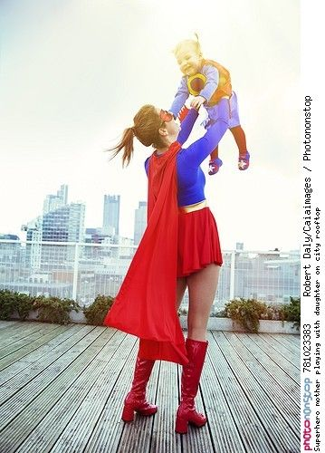 Superhero mother playing with daughter on city rooftop