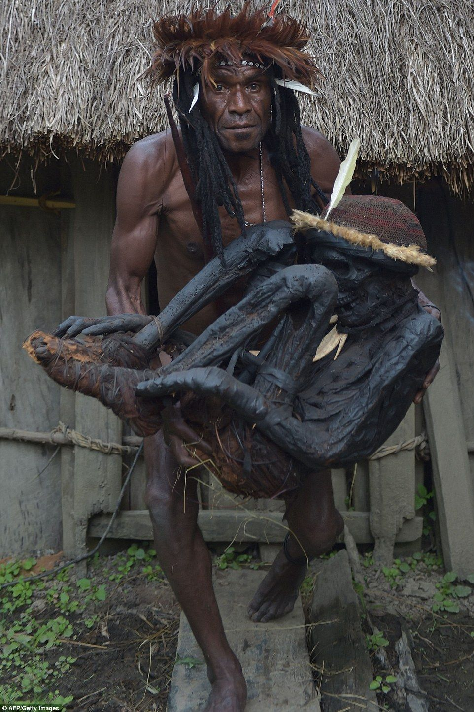 Dani tribe chief Eli Mabel is pictured holding the remains of Agat Mamete Mabel in the village of Wogi in Wamena in West Papua, an island in the centre of Papua New Guinea. The indigenous tribe, who live in a remote area of the Papuan central highlands, used to preserve their ancestors by smoking their bodies, which kept them in a near-perfect state for hundreds of years.