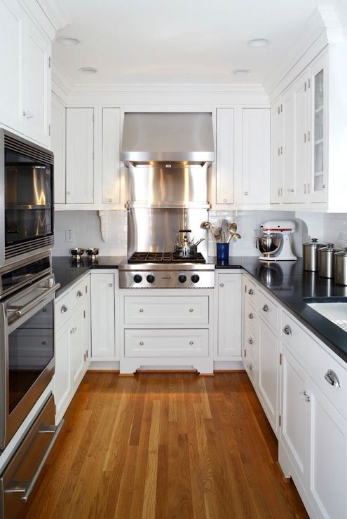 Absolute Black Granite Countertops With White Cabinetry And Honey Colored Hardwood Floors Stainless Steel Liance