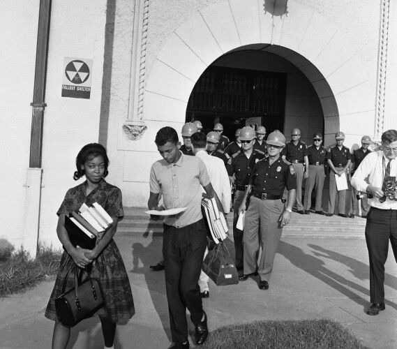With Alabama State Troopers blocking the main entrance to Murphy High School, students Dorothy Bridget Davis, 16, and Henry Hobdy, 17, arms loaded with school books, turn away from school, Sept. 9, 1963 in Mobile, Alabama. Hobdy is reading his copy of an executive order from Gov. George Wallace stopping the pair from attending classes. Murphy High is Alabama?s largest high school with 3,300 students. (AP Photo/Fred Noel)