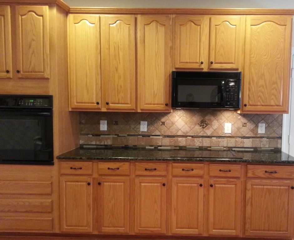 Honey oak cabinets with verde butterfly countertops for Kitchen cabinets and countertops ideas