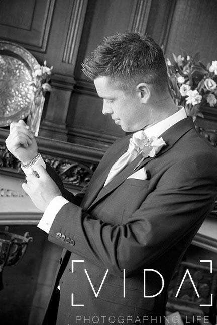 Groom adjusting cufflink at Buckland hall