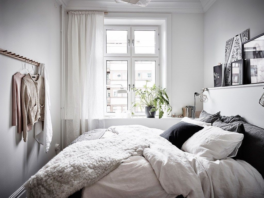 A Cozy But Small Bedroom Uses Shelving Above The Bed Bright