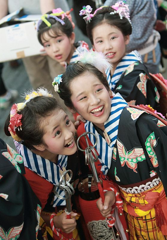 At a pause in a traditional festival parade, these girl participants laugh at a spider walking up the back of another. Chiba, Japan. PhotographerTakero Kawabata