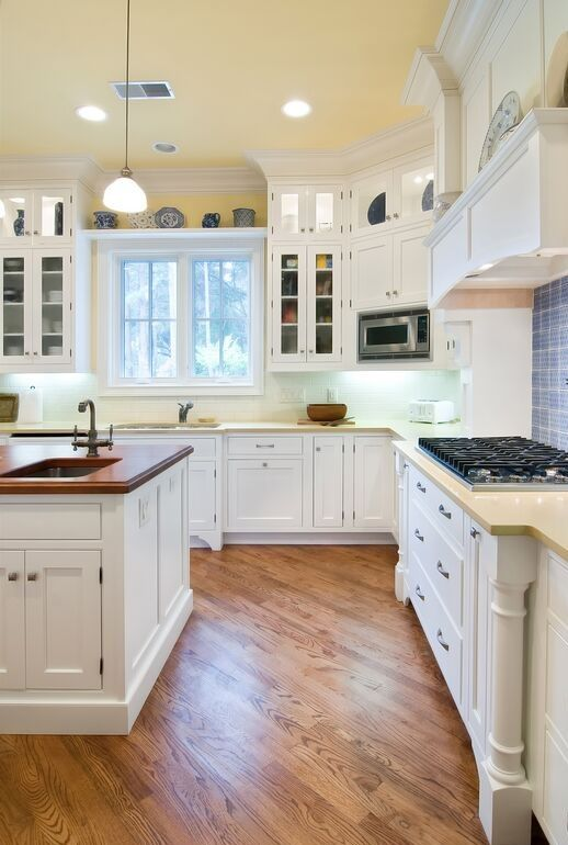 wood floors in white kitchen. elegant style informs this bold