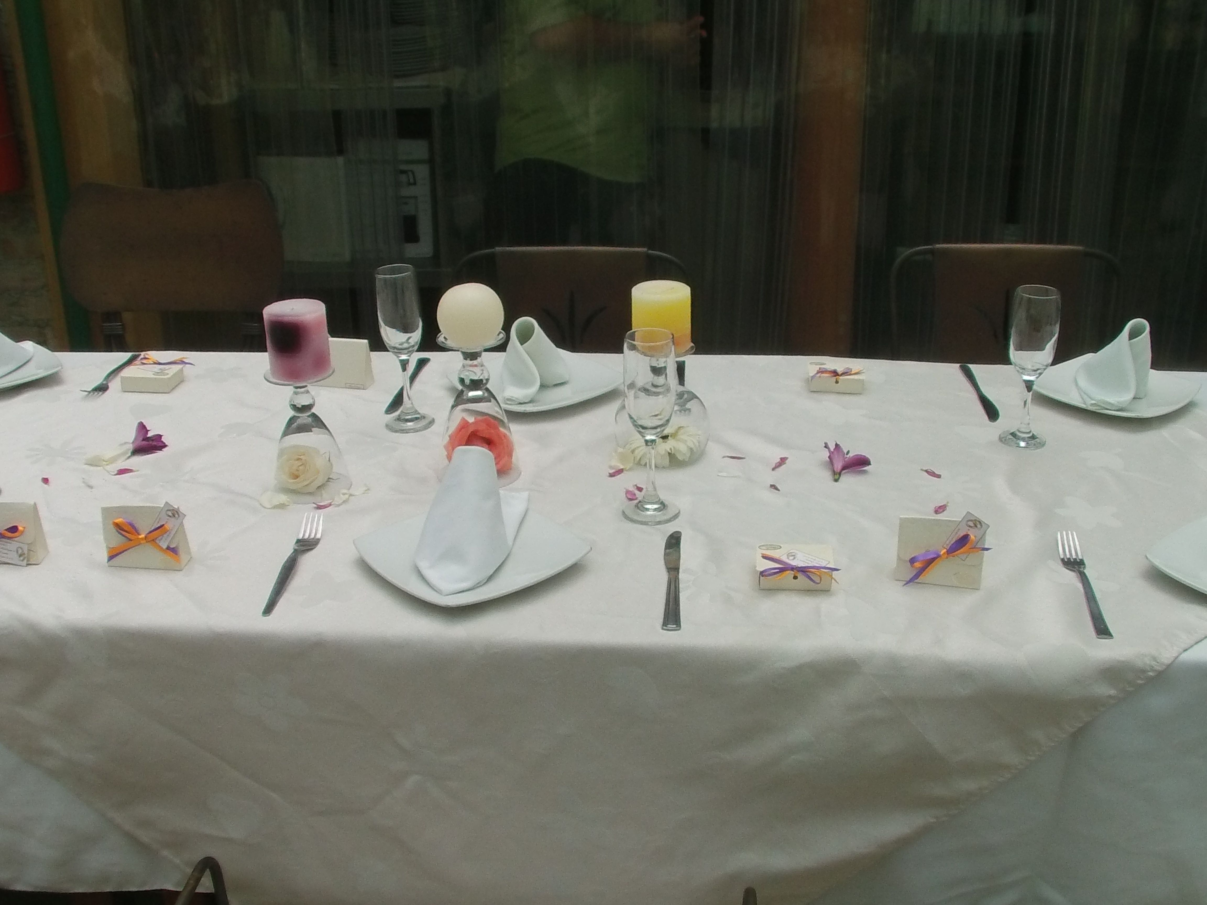 Guest tables decorated with candles, flowers, cups and boxes of almonds to identify the seats
