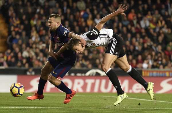 Barcelona's defender Jordi Alba (L) vies with Valencia's Brazilian defender Gabriel during the Spanish league football match Valencia CF against FC Barcelona at the Mestalla stadium in Valencia on November 26, 2017. / AFP PHOTO / JOSE JORDAN