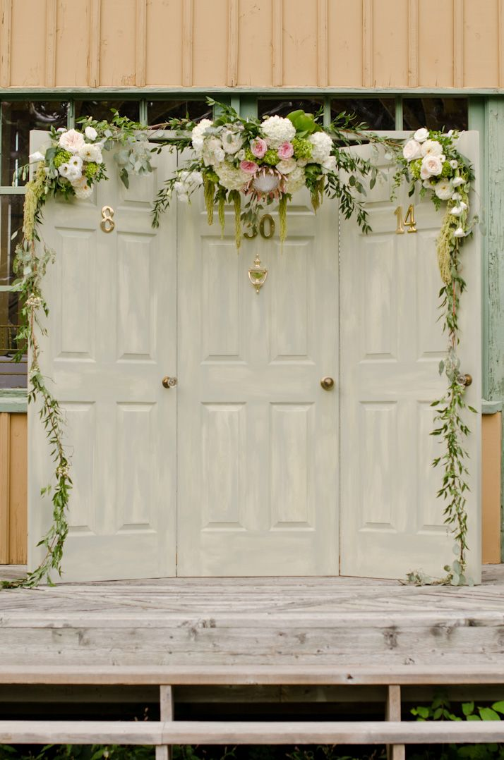 Vintage door with gold number and knob wedding backdrop wth fresh floral arbor