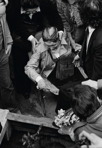The saddest day of her life. Simone de Beauvoir throws a posy of flowers into the grave of Jean-Paul Sartre during his funeral in Paris, 1980. Photo: Mansour Nasiri.