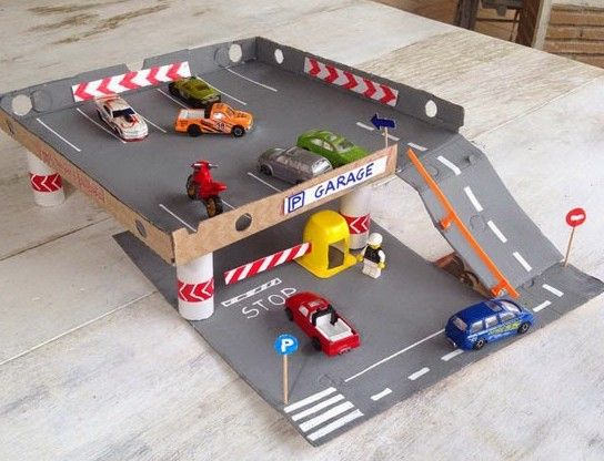 Use a pizza box to make a cardboard parking garage! The craft value and play value here is huge. Great DIY crafts for parents to do with kids. #parenting
