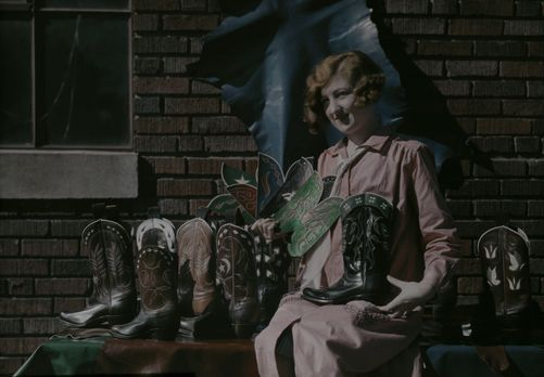 832038. A woman displays varying stock models of a cowboy boot manufacturer. Fort Worth, Texas