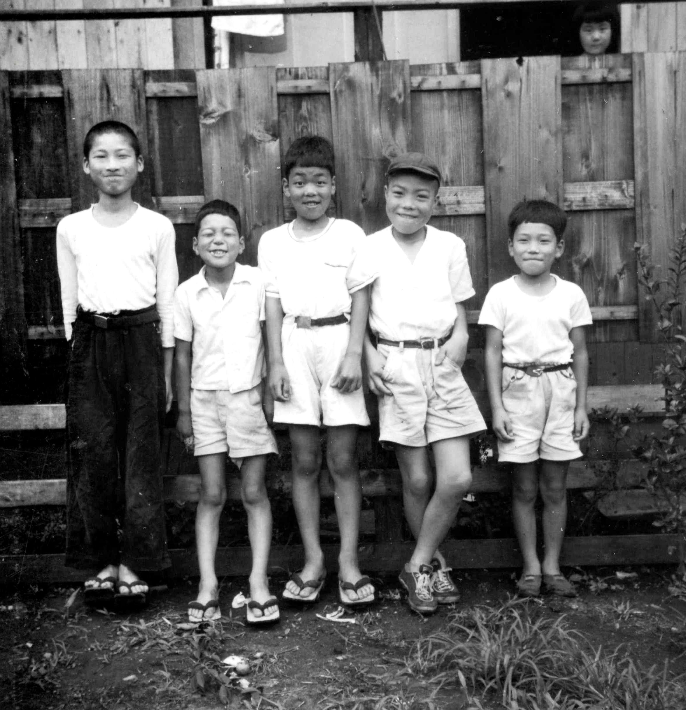 smiling boys against a fence. Japan