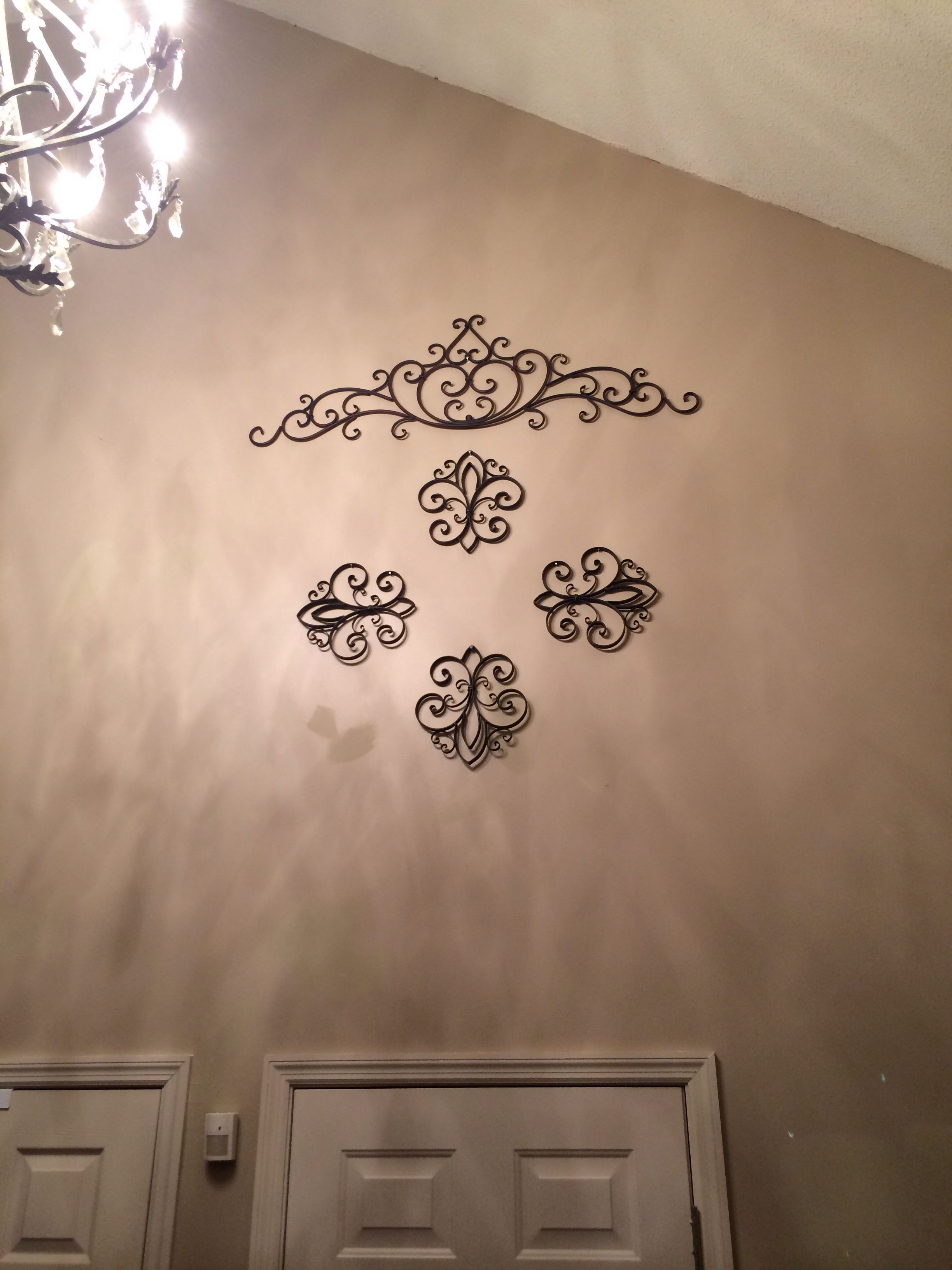 Arrange metal wall art to fill large empty wall space two story