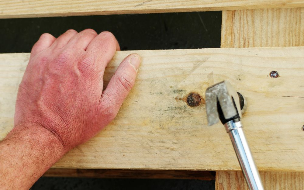 A person using a hammer and lumber to mount a gas tankless
