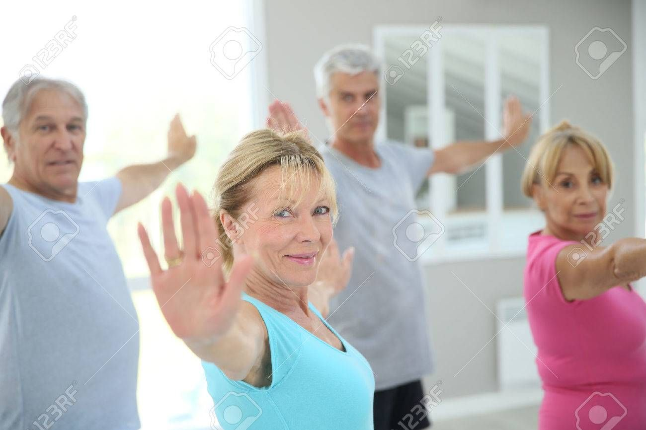 Senior people stretching out in fitness room ,
