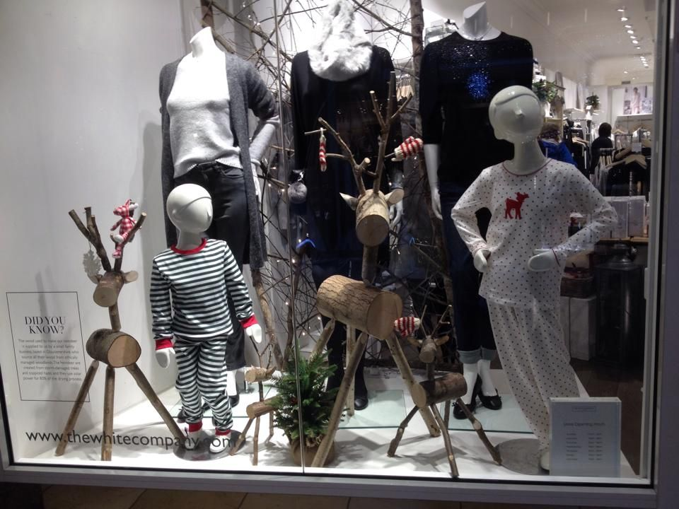 A family of our rustic log deer displayed in The White Company's shop window in Cambridge / Christmas shop display / visual merchandising / available from www.thelogbasket.co.uk