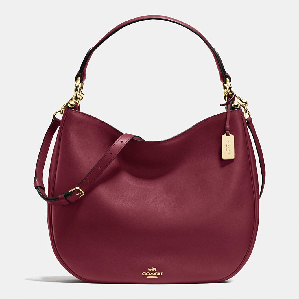 Soft and slouchy in supple glove-tanned leather, this simple, graceful silhouette is dressed up with striking hardware, including a polished metal hangtag. Zip and open pockets organize its luxuriously leather-lined interior; the adjustable strap detaches for multiple wearing options.