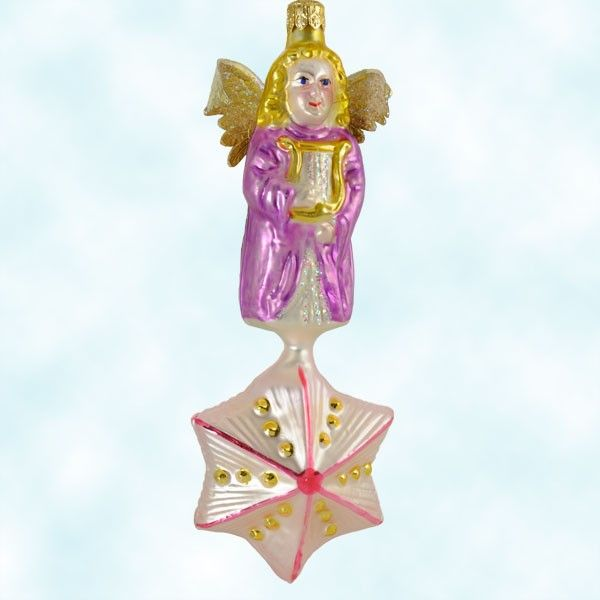 A lovely old-fashioned Radko Angelique Christmas Ornament, atop a star & with pert golden paper wings