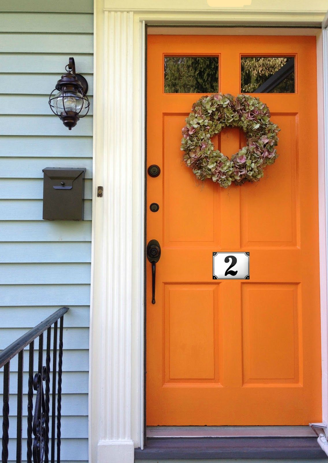 orange door with pale blue or pale gray siding love it house
