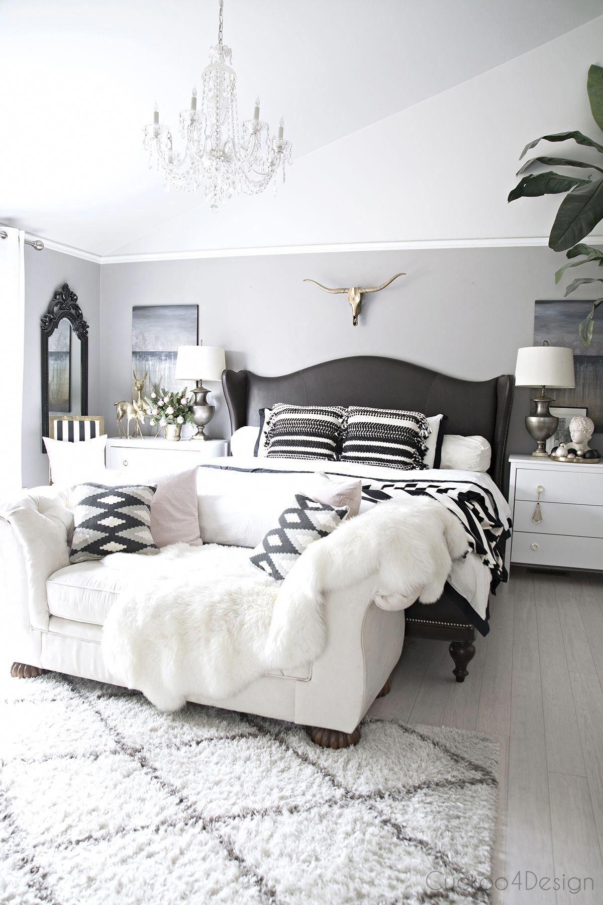 beautiful serene bedroom with leather wingback bed | brass longhorn skull | cathedral ceilings | crystal chandelier | blush and black and white accents #whitebedroom #graybedroomwithpopofcolor beautiful serene bedroom with leather wingback bed | brass longhorn skull | cathedral ceilings | crystal chandelier | blush and black and white accents #whitebedroom #graybedroomwithpopofcolor