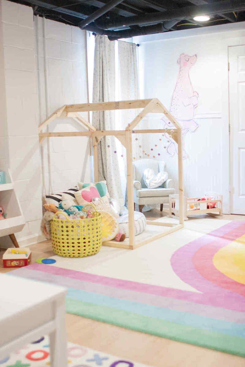Salle de jeu pour fille en blanc et tons pastel avec maison en bois pouf et panier à jouets