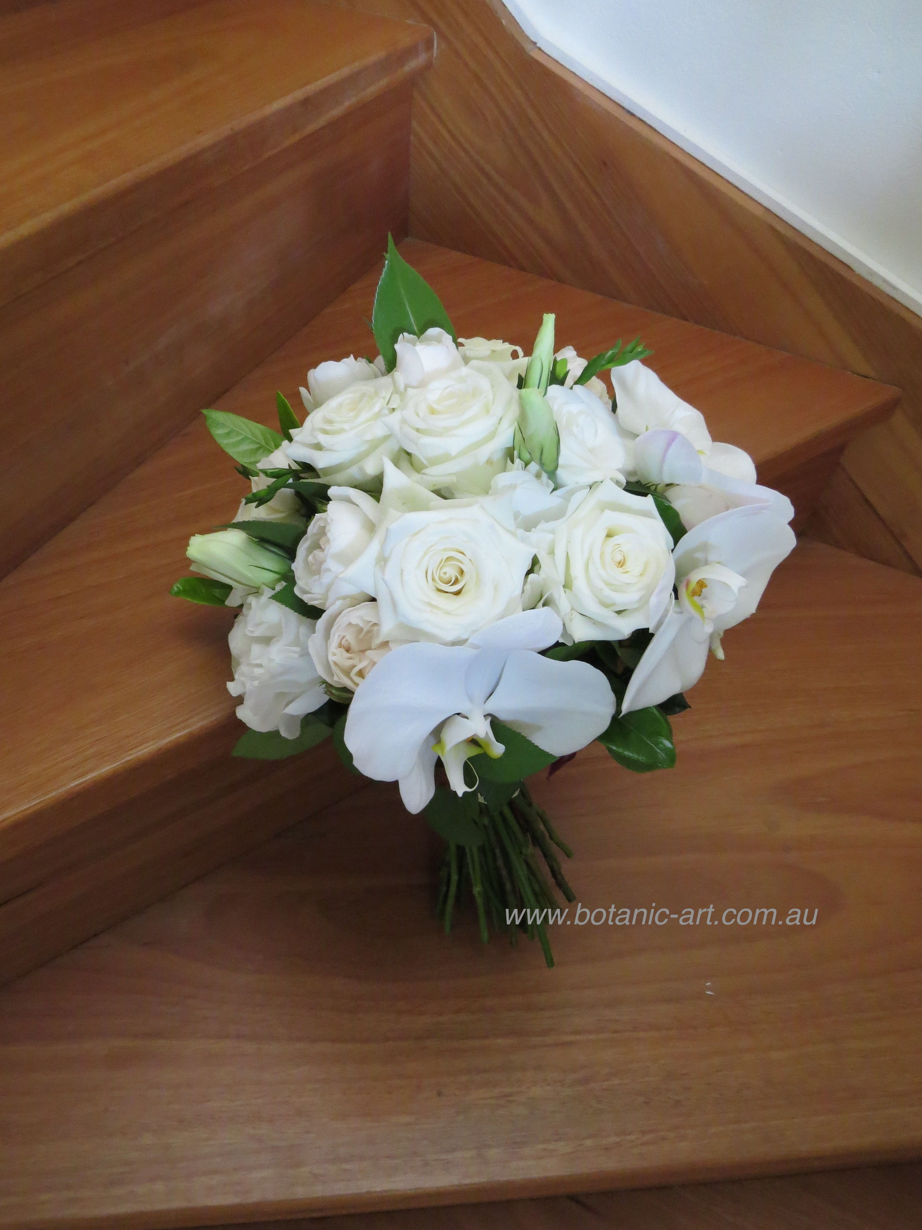roses and phalanophsis orchids with a touch of green is