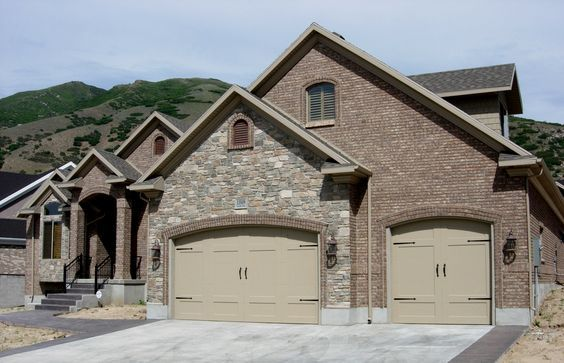 The light hue of this steel garage door contrasts very well with the surrounding darker stones and bricks providing a slightly rustic feel for a classic home.