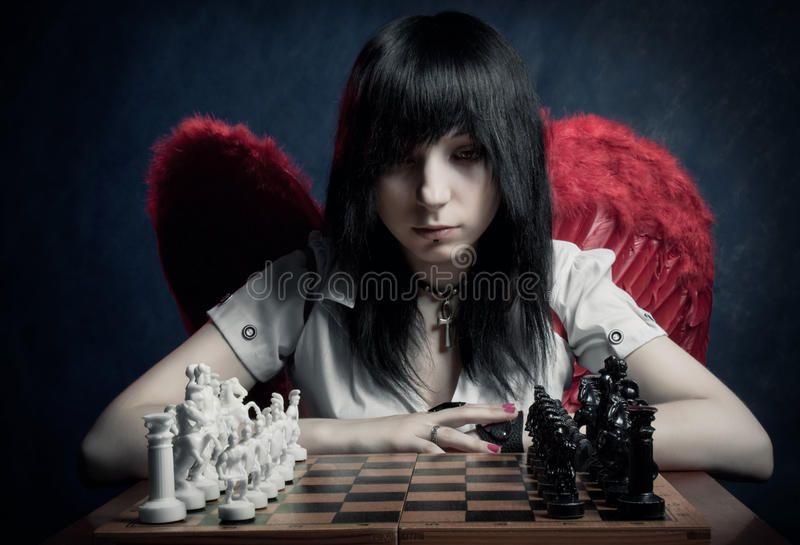 Chessmaster. Pretty angel looking to chessboard over dark background ,