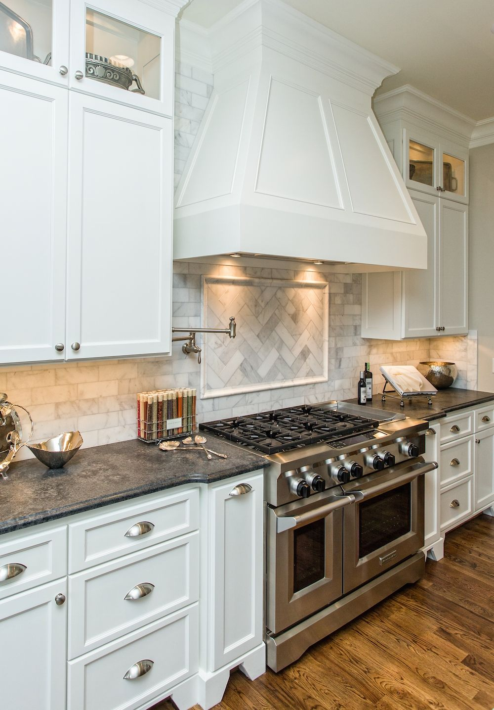 A beautiful white kitchen with marble backsplash and gas range in ...