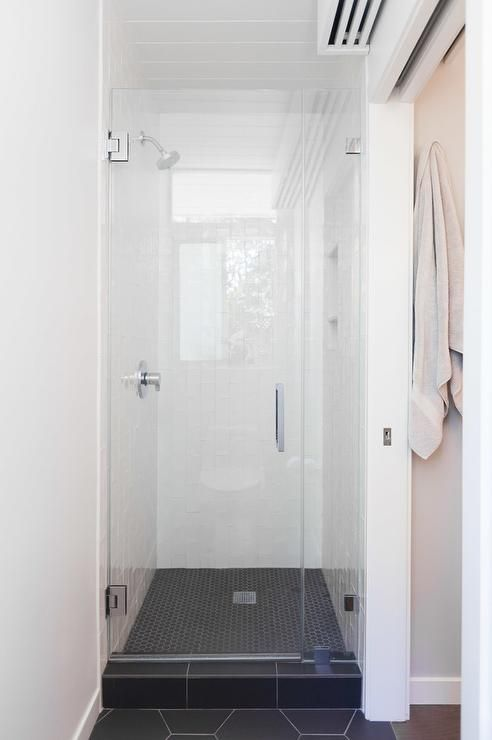 Small Chic Shower Features White Grid Tiles Over A Black Hex Tile