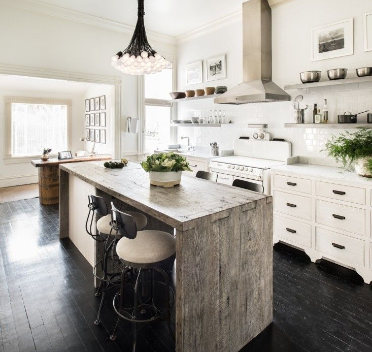 Reclaimed wood island, modern lighting, and a vintage range mix effortlessly in this charming San Francisco Victorian.